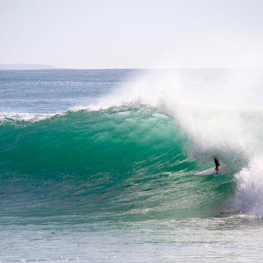 """Ein Surfer reitet auf einer Welle bei """"Supertubos"""""""