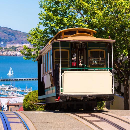 """Typische Cable Car und die Gefängnisinsel """"Alcatraz"""" im Hintergrund"""
